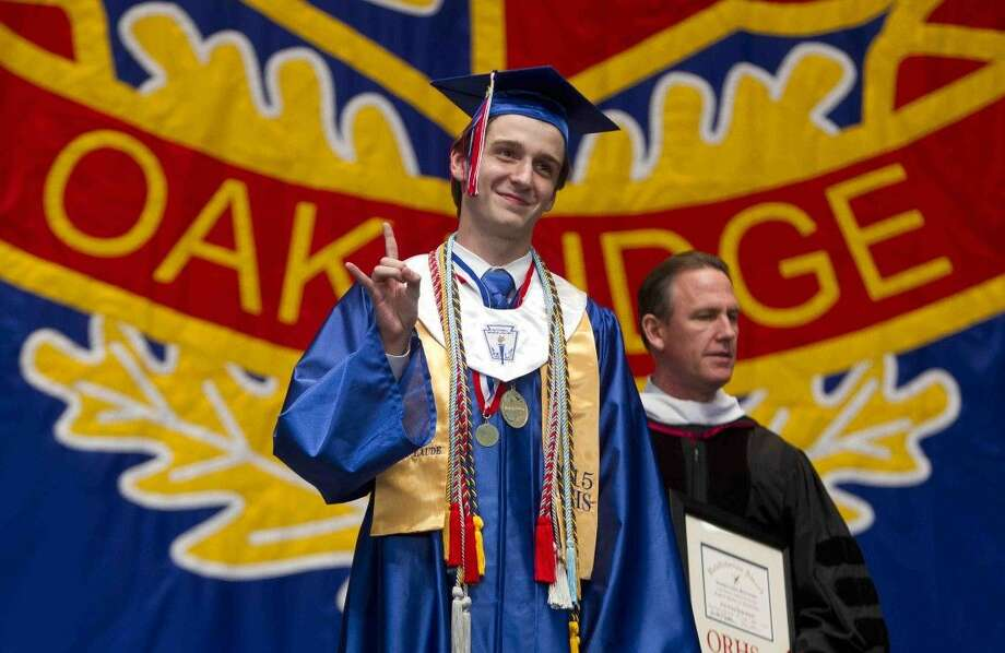 Valedictorian Jonathan McClanahan gives a hook 'em sign during a graduation ceremony at the Cynthia Woods Mitchell Pavilion Wednesday. Photo: Jason Fochtman