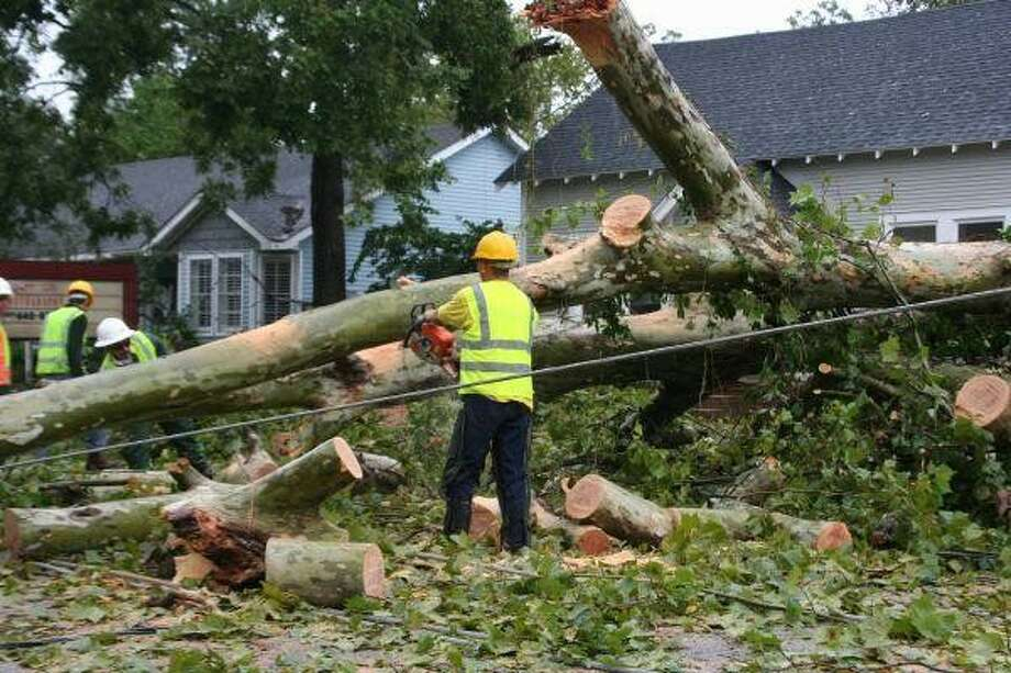 Humble city workers tackle a tree ensnarled in power lines after Hurricane Ike trounced the Houston area. Photo: STEFANIE THOMAS