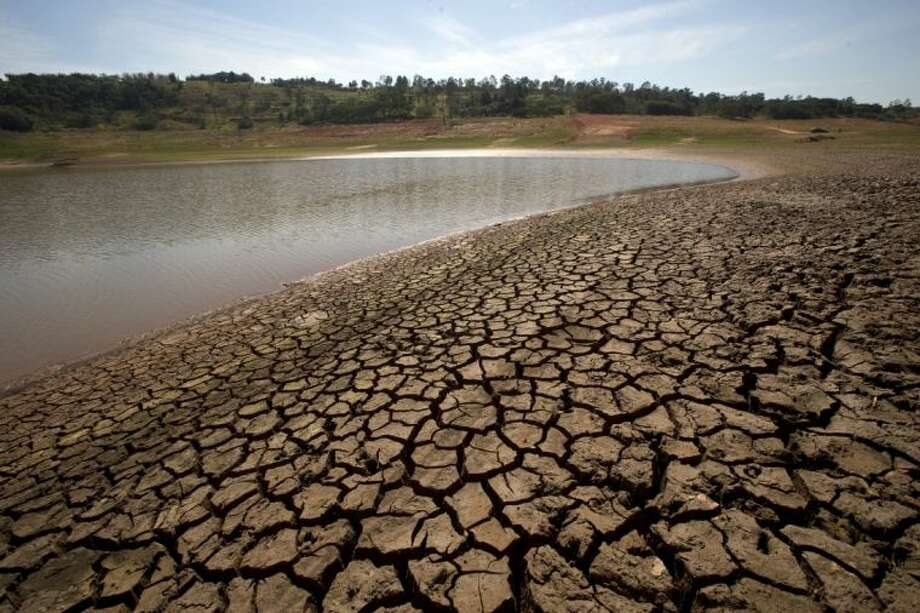 This May 14 photo shows cracked earth where there once was water at the Jaguari dam, which is part of the Cantareira System responsible for providing water to the Sao Paulo metropolitan area, in Braganca Paulista, Brazil. The worst drought in more than 80 years is hitting Sao Paulo, Brazil's largest city, just as it prepares for the tens of thousands of foreigners expected at the tournament opener. Photo: Andre Penner