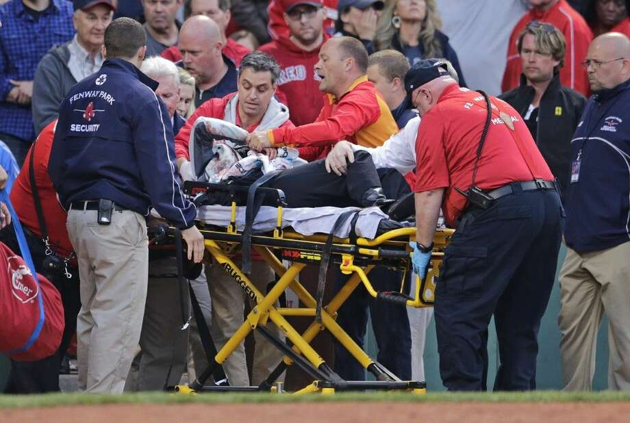A fan, who was accidentally hit in the head with a broken bat by Oakland Athletics' Brett Lawrie, is helped from the stands during a baseball game against the Boston Red Sox at Fenway Park in Boston, Friday. Photo: Charles Krupa