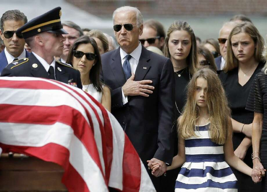 Vice President Joe Biden, accompanied by his family, holds his hand over his heart as he watches an honor guard carry a casket containing the remains of his son, former Delaware Attorney General Beau Biden, into St. Anthony of Padua Roman Catholic Church in Wilmington, Del., Saturday for funeral services. Photo: Patrick Semansky
