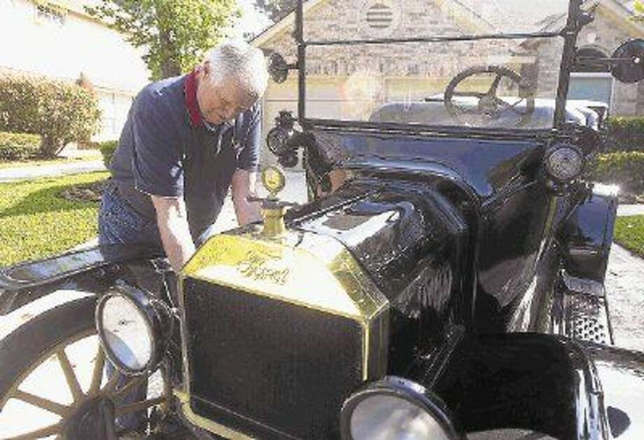 Woodlands resident Bill Severn tinkers with his 100-year-old Ford Model T outside his residence.