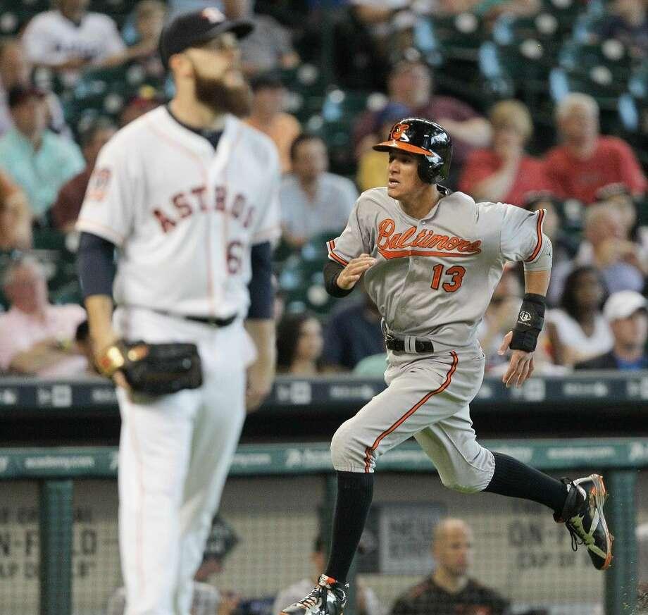 Baltimore Orioles' Manny Machado scores in the first inning as Houston Astros' Dallas Keuchel watches the ball during a baseball game, Thursday in Houston. Photo: Bob Levey