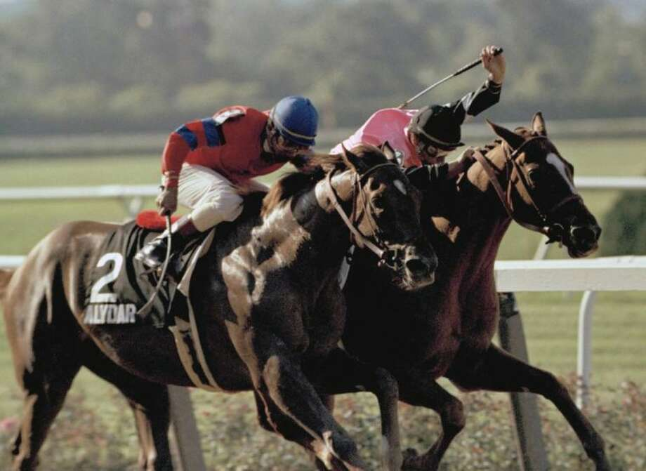 Steve Cauthen raises his whip to speed Affirmed toward the finish line as Alydar is driven home by Jorge Velasquez in the final stretch of the Belmont Stakes on June 12, 1978, at Belmont Park in Elmont, New York. Photo: Perez