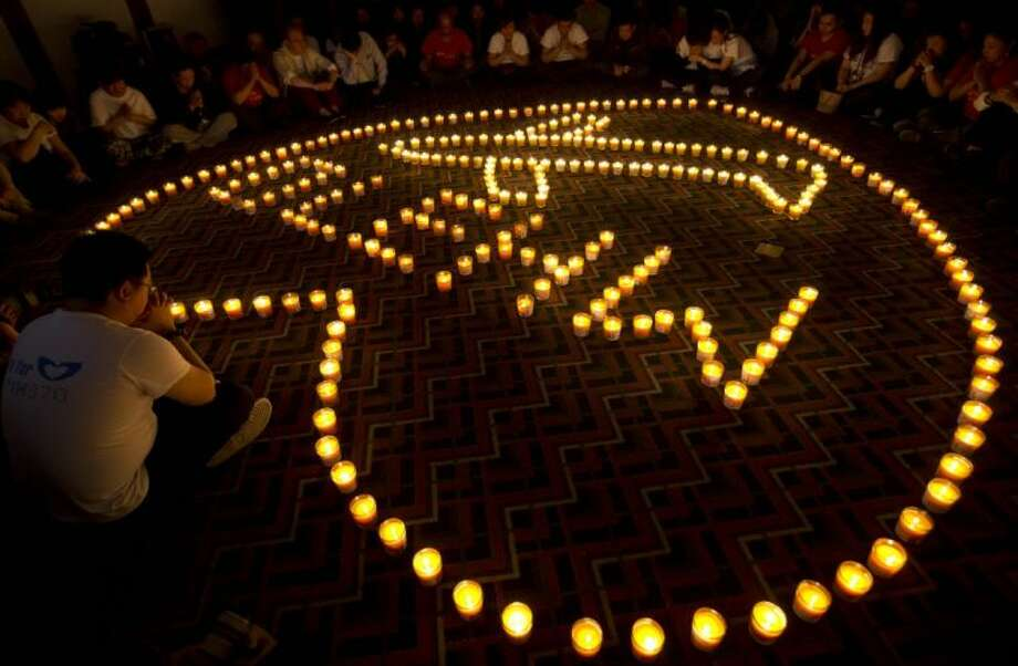 In this April 8 file photo, relatives of Chinese passengers onboard Malaysia Airlines Flight 370 offer prayers during a candlelight vigil for their loved ones at a hotel in Beijing, China.