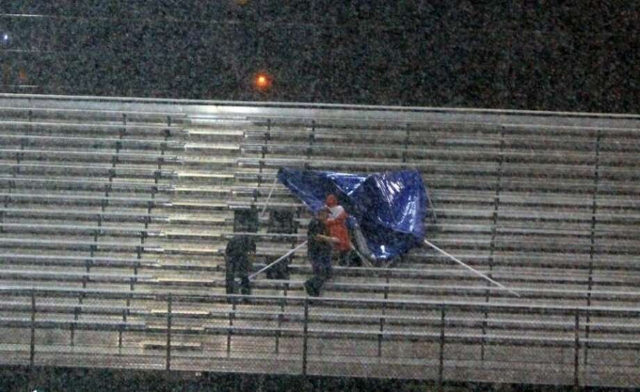 These were the only people who braved coming in the stadium on Friday night. They tried to erect a tent, but the wind and the rain brought failure to their project. Photo: MARK ANDERSON