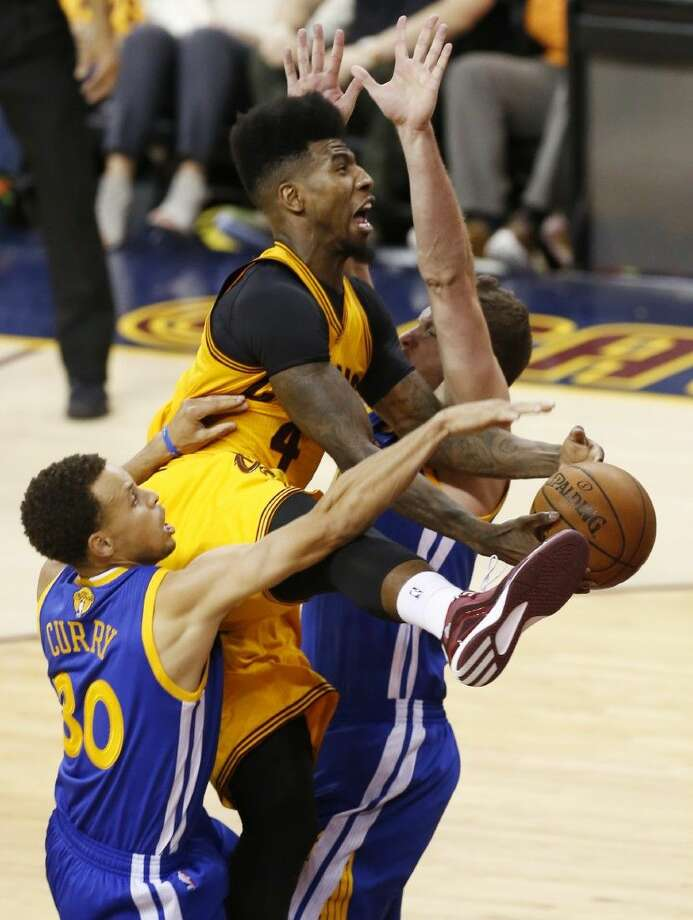 Cleveland Cavaliers guard Iman Shumpert, center, crashes into Golden State Warriors guard Stephen Curry, left, and forward David Lee during the second half of Game 3 of basketball's NBA Finals in Cleveland, Tuesday. Photo: Paul Sancya