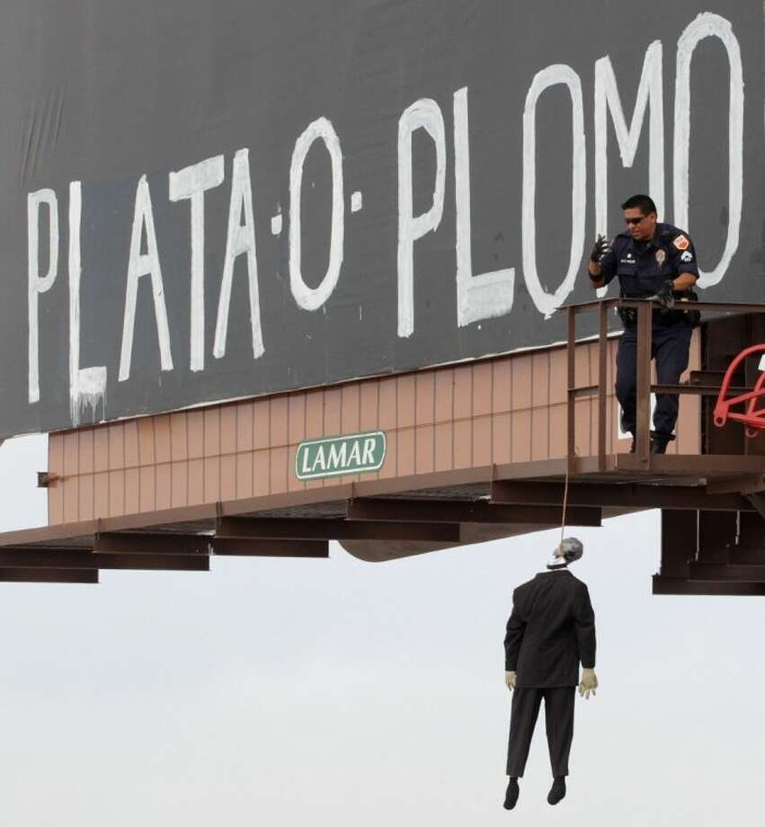 "An El Paso, Texas police officer checks a makeshift mannequin Thursday, May 22, 2014, which was left hanging on a billboard along with the message, ""silver or lead"" in Spanish, a threat heard in Mexico signifying pay up or get shot. El Paso police were investigating two mysterious messages painted onto billboards in the border city that included mannequins dressed in suits hanging from nooses. Photo: Victor Calzada"