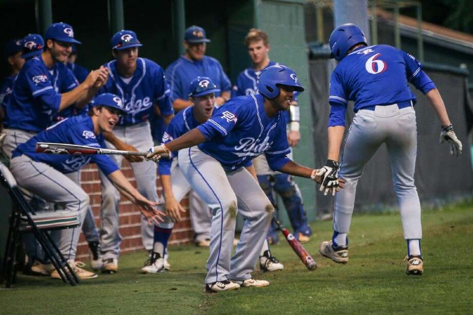 Oak Ridge players celebrate after scoring a run during the high school baseball game against The Woodlands this past Friday night. Photo: Michael Minasi