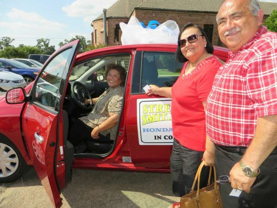 Sacred Heart Catholic Church Springfest Chairs Manuel and Herlinda Gonzalez present Yolanda Piert with the 2014 Nissan Versa she won this month in the raffle drawing at the church's annual Spring Festival.