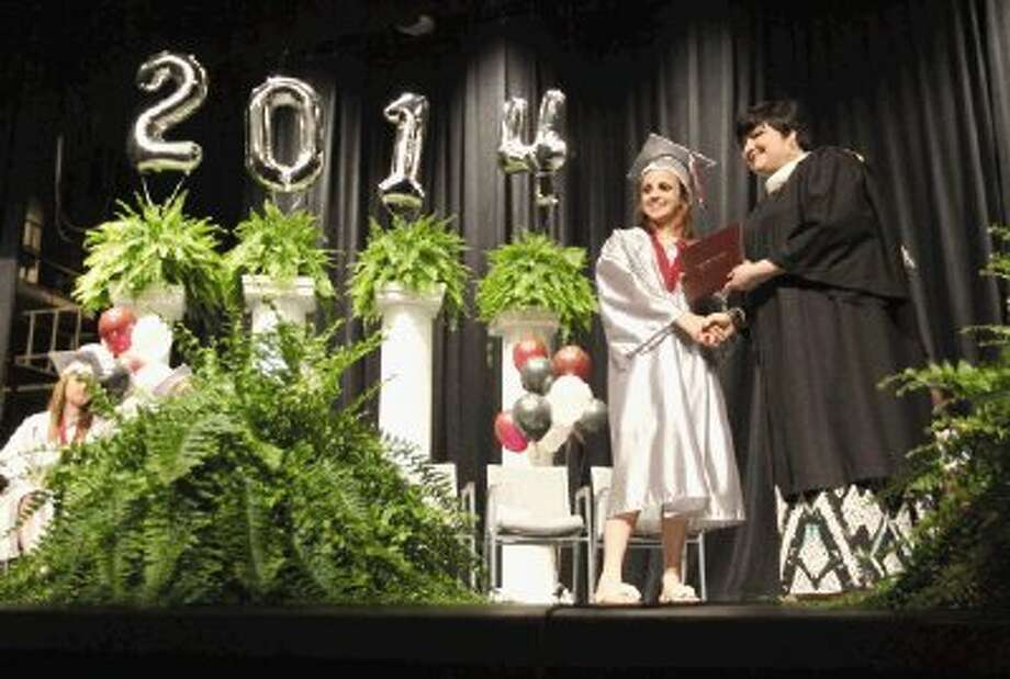 Austin Buffington receives her high school diploma during the Hauke High School graduation ceremony at Conroe High School Thursday. Go to HCNPics.com to view and purchase this photo, and others like it. Photo: Jason Fochtman