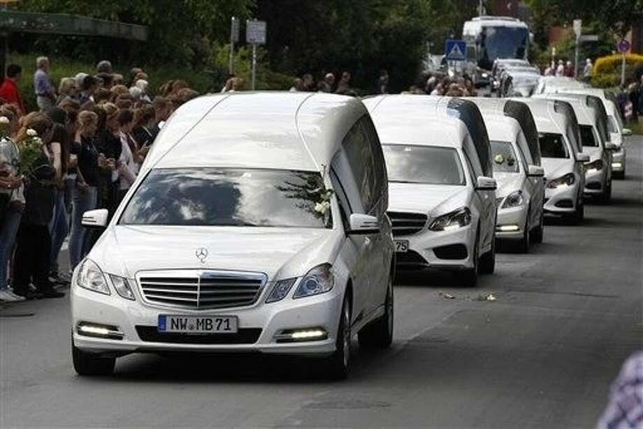 White hearses carrying the remains of pupils killed in the Germanwings plane crash in France are about to pass by the Joseph-Koenig high school in Haltern, Germany, Wednesday. 150 people died in the plane crash on March 24.
