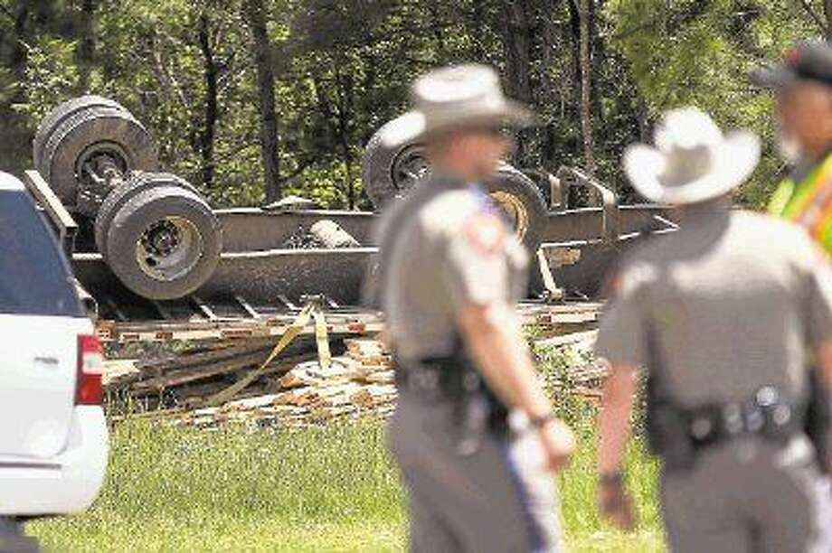 Law enforcement examine the three-vehicle crash scene where three people died and one child was injured Friday on Texas 105 East near South Walker Road. Photo: Michael Minasi
