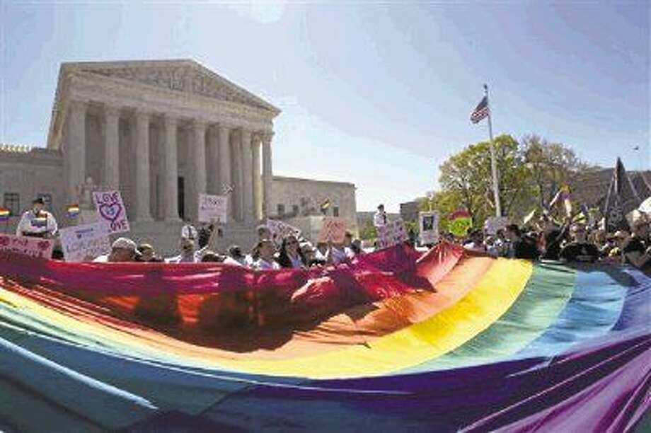 FILE - In this April 2015 file photo, demonstrators stand in front of a rainbow flag of the Supreme Court in Washington, as the court was set to hear historic arguments in cases that could make same-sex marriage the law of the land. Gay and lesbian couples could face legal chaos if the Supreme Court rules against same-sex marriage in the next few weeks. Same-sex weddings could come to a halt in many states, depending on a confusing mix of lower-court decisions and the sometimes-contradictory views of state and local officials. Among the 36 states in which same-sex couples can now marry are 20 in which federal judges invoked the Constitution to strike down marriage bans. Photo: Jose Luis Magana