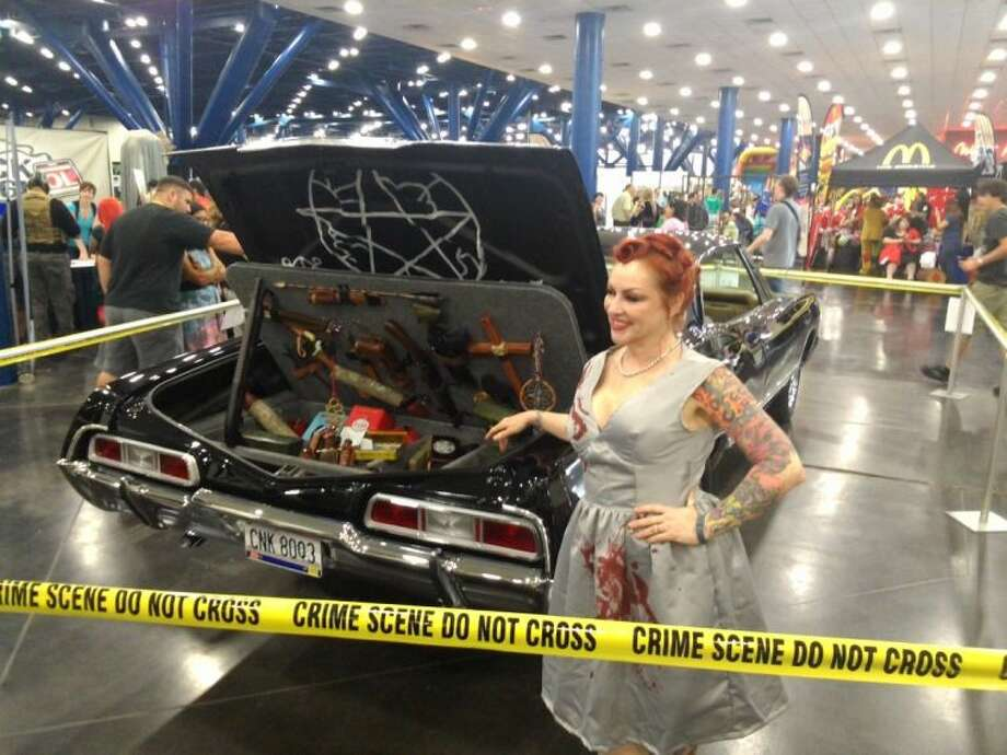 "A cosplayer (short for costume player, is a performance art where participants wear costumes and accessories to represent a specific character) dressed as Abbadon from the CW series ""Supernatural"" poses with the weapons trunk of Magnolia couple Adam and Lisa Diamont's replica of ""Baby,"" the 1967 Chevy Impala from the series at Comicpalooza 2014 at the George R Brown Convention Center Memorial Day weekend."
