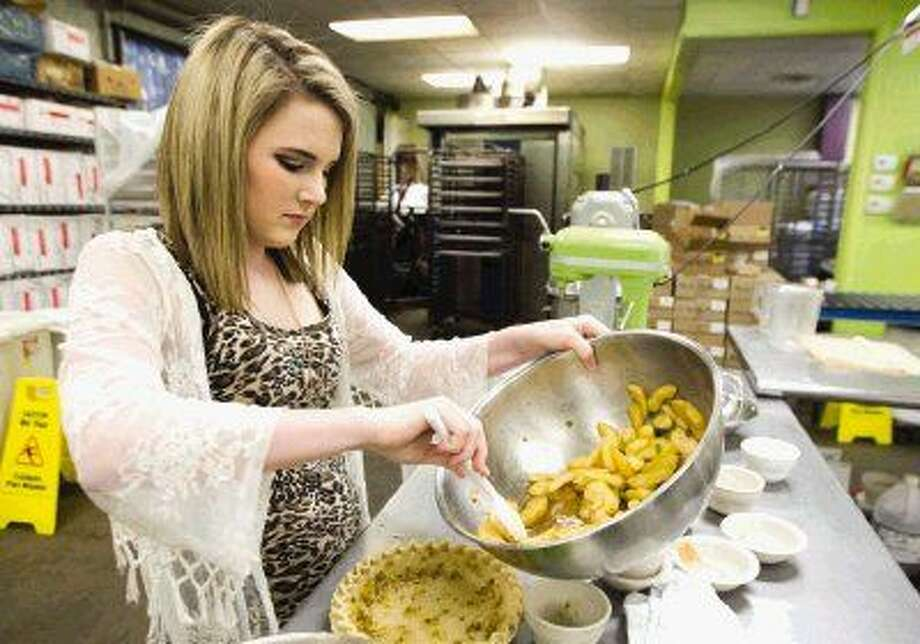 Montgomery High School junior Lauren Williams works on the filling for her Rodeo Grand Champion pie recipe in the kitchen of local eatery Pie in the Sky Co. Photo: Jason Fochtman