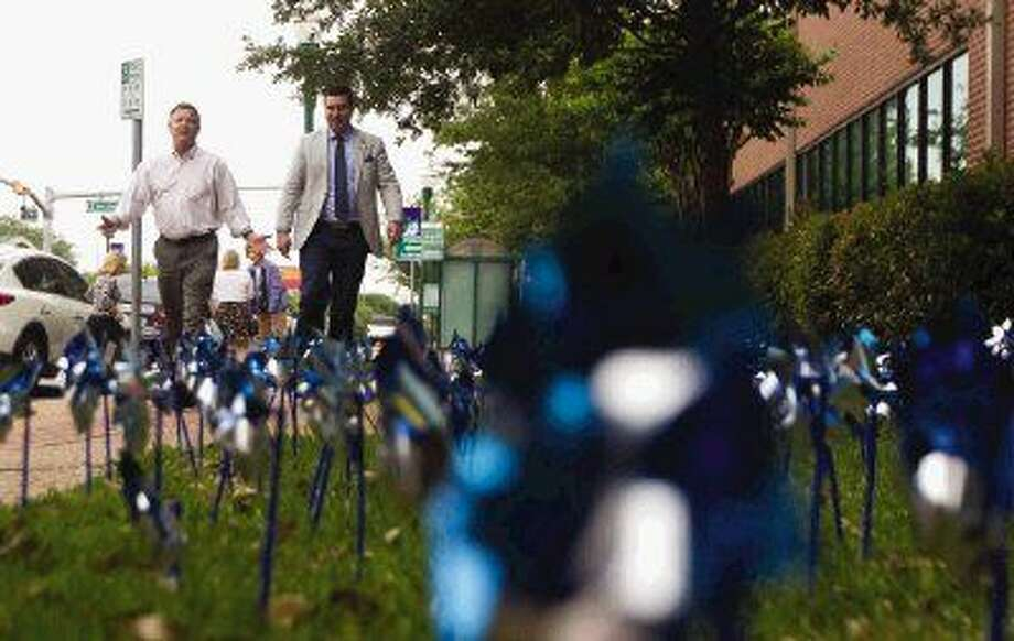 Children's Safe Harbor Board President Ron Leach and Montgomery County Assistant District Attorney Vince Santini walk along a sea of pinwheels in downtown Conroe Tuesday. To recognize the victims of sexual abuse, Safe Harbor joined community leaders in displaying 966 pinwheels on the grounds of the Alan B. Sadler Administrative Building.