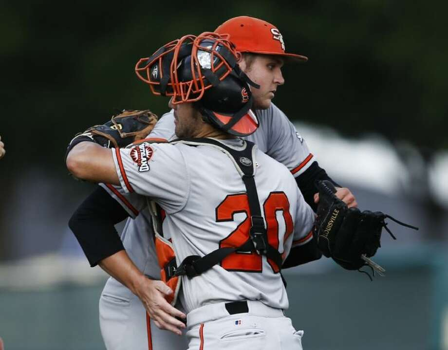 Sam Houston State catcher Anthony Azar of The Woodlands congratulates relief pitcher Alan Scott following the Bearkats' 2-1 win over Dallas Baptist on Friday in an NCAA regional tournament game in Fort Worth.