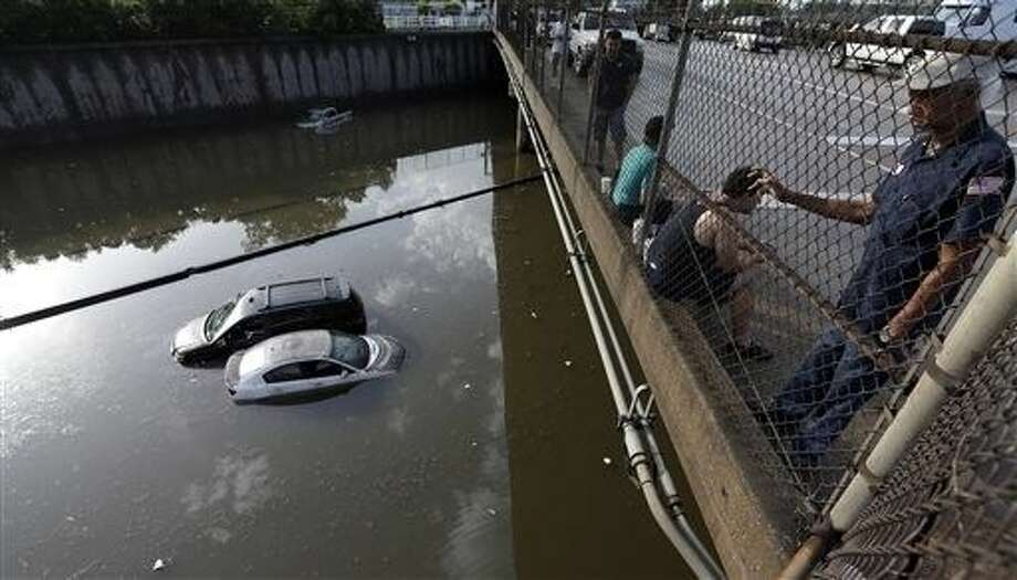 Cars sit in floodwaters along Interstate 45 after heavy overnight rain flooded parts of the highway in Houston, Tuesday, May 26. The Colorado River in Wharton and the Brazos and San Jacinto rivers near Houston are the main focus of concern as floodwaters move from North and Central Texas downstream toward the Gulf of Mexico.