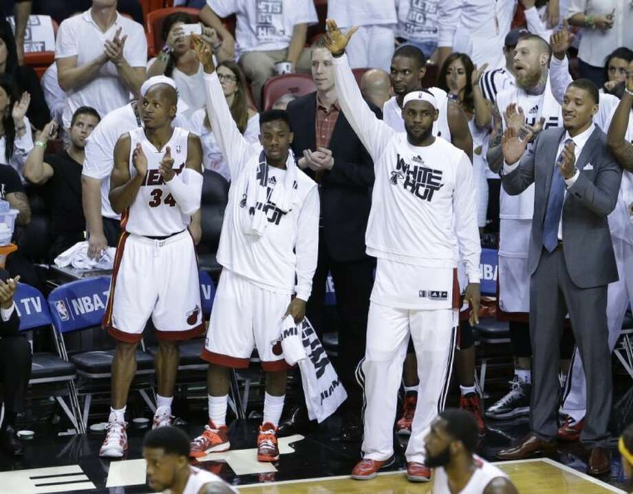 Miami Heat players, from left, Ray Allen, Norris Cole and LeBron James cheer during the last seconds of Game 6 in the Eastern Conference finals on Friday in Miami. Photo: Wilfredo Lee