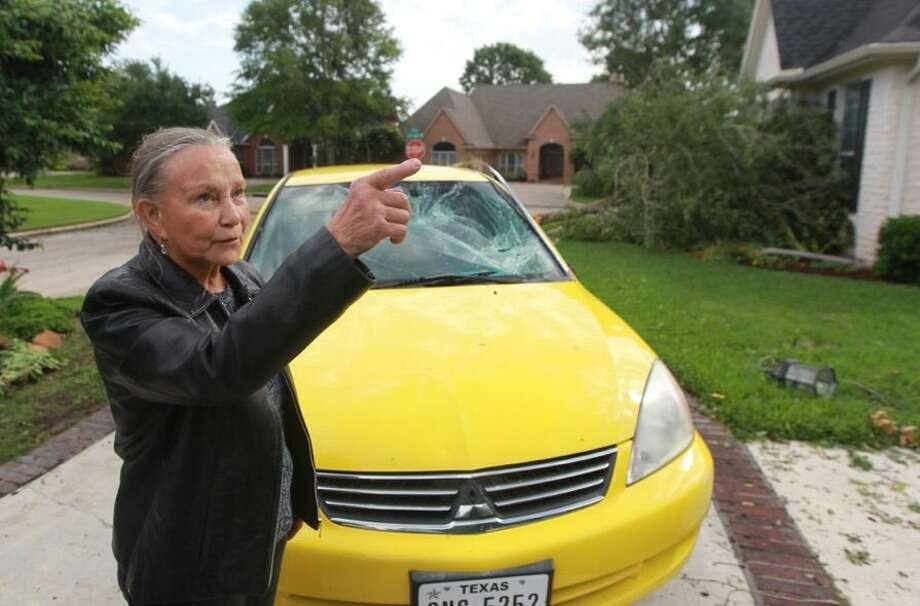 Ruth Vicchio, a resident of Bentwater, stands by her car, which sustained damaged after last night's storm. Photo: Jason Fochtman/The Courier