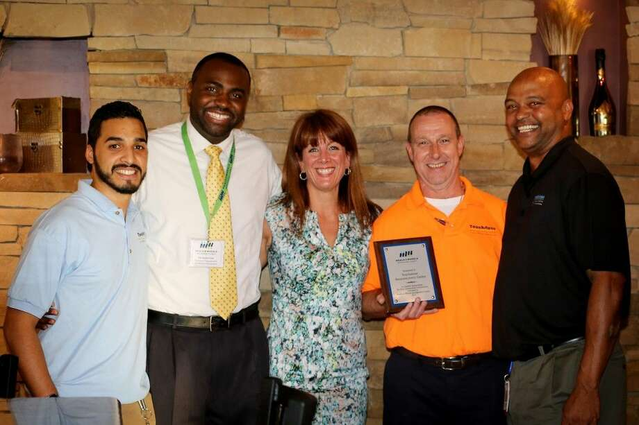 From left to right: Steve Perez, De'Andre Guin, Allison Hulett, Tom Owens, Don Williams. Hulett, Executive Director of Meals on Wheels Montgomery County and Guin present a plaque of appreciation to staff of Touchstone Neurorecovery Center for their generous donation to the organization.