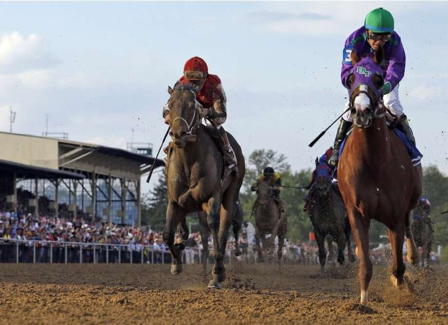 California Chrome, right, with Victor Espinoza up, wins the 139th Preakness Stakes ahead Ride on Curlin on May 17 at Pimlico Race Course in Baltimore. Photo: Matt Slocum