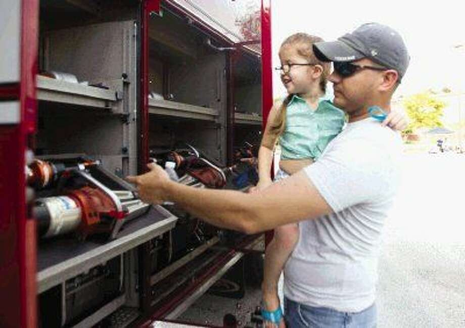 Estevan Leal shows his daughter, Aubrie, fire nozzles at the Local Heroes event at Montgomery County Central Library Thursday. Go to HCNpics.com to view more photos from the event. Photo: Jason Fochtman