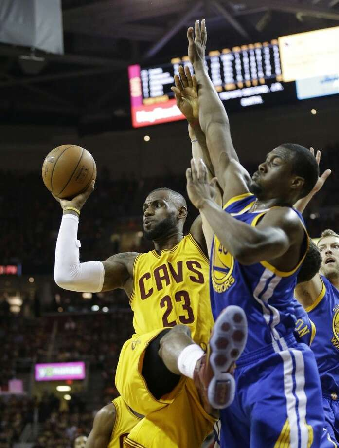 Cleveland Cavaliers forward LeBron James, left, makes a pass under pressure from Golden State Warriors forward Harrison Barnes during Game 4 of the NBA FInals. The Warriors rolled to a 103-82 victory, tying the series at two games each. Photo: Tony Dejak