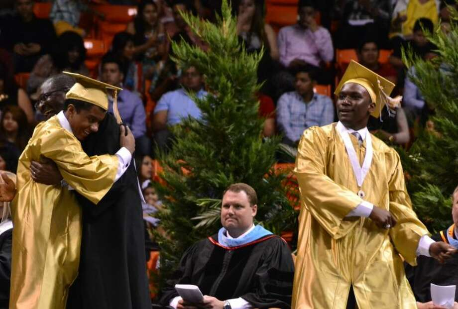 One 2014 Conroe High graduate does a celebration dance as another hugs a Conroe ISD administrator during the Saturday morning graduation ceremony at Sam Houston State University in Huntsville. More than 700 graduates walked the stage during the 112th graduation ceremony of Conroe High School.