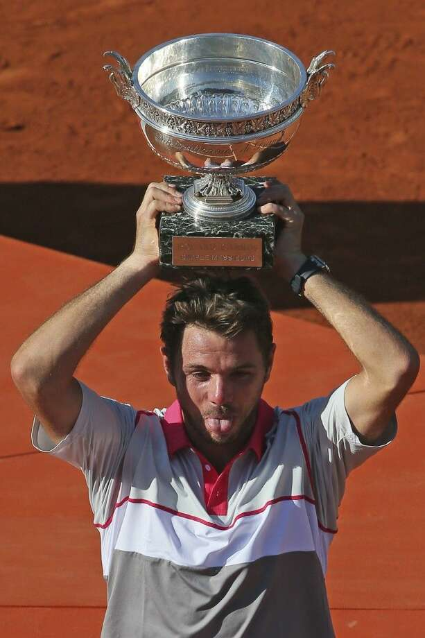 Switzerland's Stan Wawrinka sticks out his tongue as he holds the trophy after winning the men's final of the French Open at the Roland Garros stadium, in Paris, France, Sunday. Photo: David Vincent