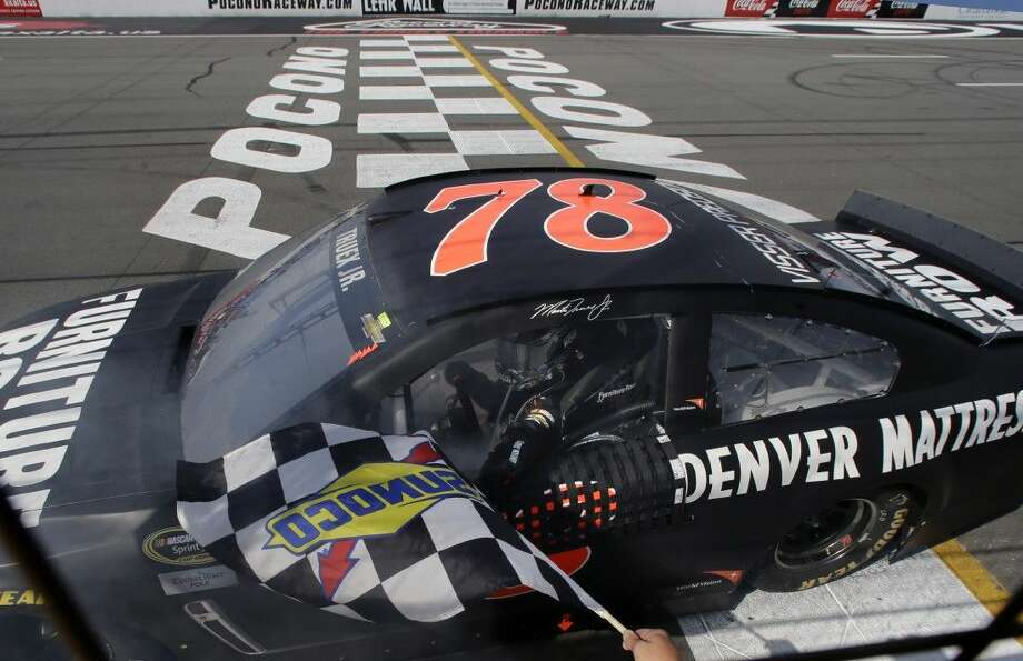 Martin Truex Jr. reaches for the checkered flag after winning a NASCAR Sprint Cup Series auto race at Pocono Raceway in Long Pond, Pa., Sunday Photo: Mel Evans