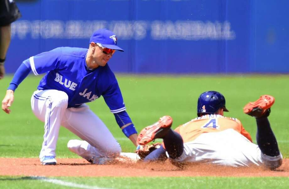 Toronto Blue Jays second baseman Ryan Goins, left, tags out Houston Astros' George Springer on stolen base-attempt during first-inning on Sunday. Photo: Frank Gunn