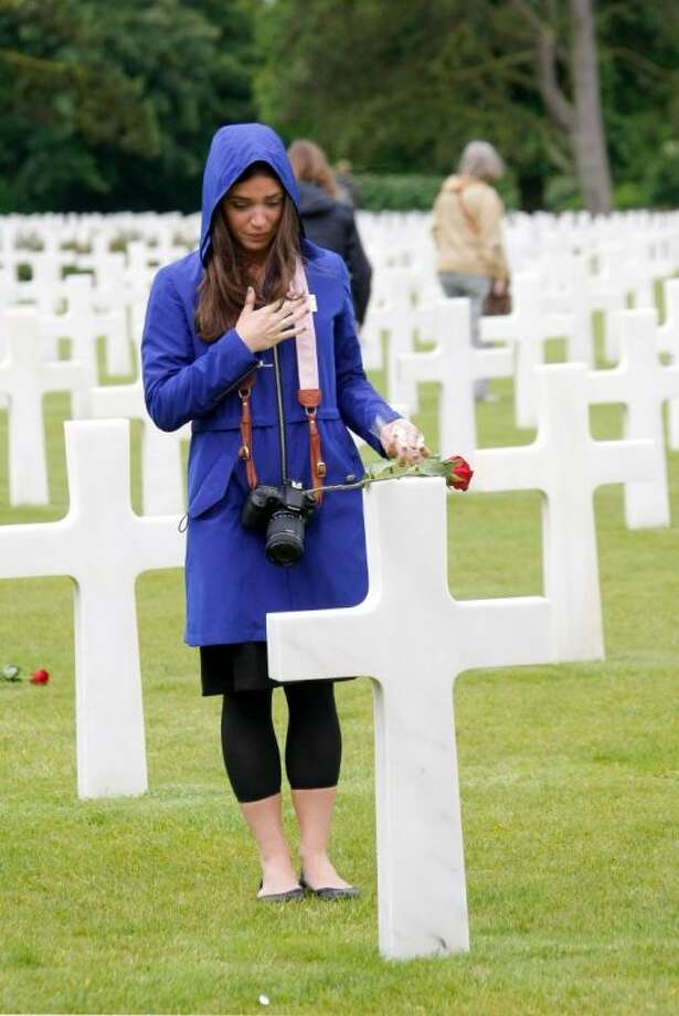 Marissa Neitling, 30, from Lake Oswego, Oregon, places a flower on a grave in the Normandy American Cemetery and Memorial, in Colleville sur Mer, France, Wednesday.
