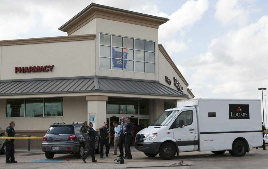In this Sept. 6, 2013 photo, police investigate an armored car robbery at the Walgreens in Houston. Eleven armored trucks were robbed in Houston in 2013 and another eight last year, accounting for 20 percent of all such heists in the U.S. In 2013, 120 banks were robbed around Houston, one every three days. Photo: J. Patric Schneider