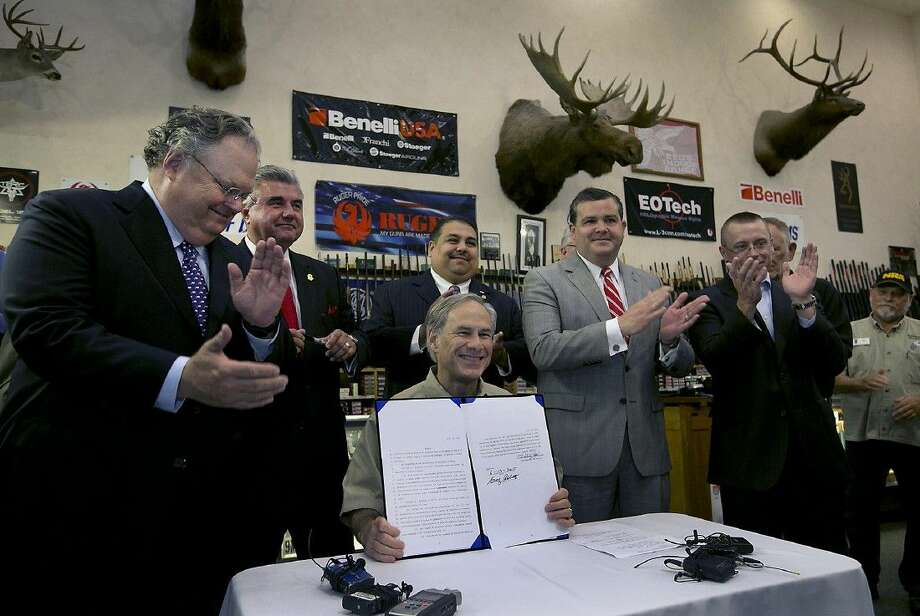 Texas Gov. Greg Abbott signs into law bills letting Texans carry concealed handguns on college campuses and openly carry them virtually everywhere else at Red's Indoor Range in Pfulgerville Saturday. Photo: Ralph Barrera