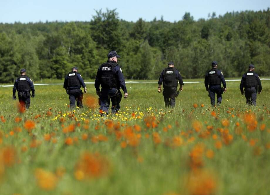 Law enforcement officers walk in a field along Route 3 on Saturday in Saranac, N.Y. Photo: Mike Groll