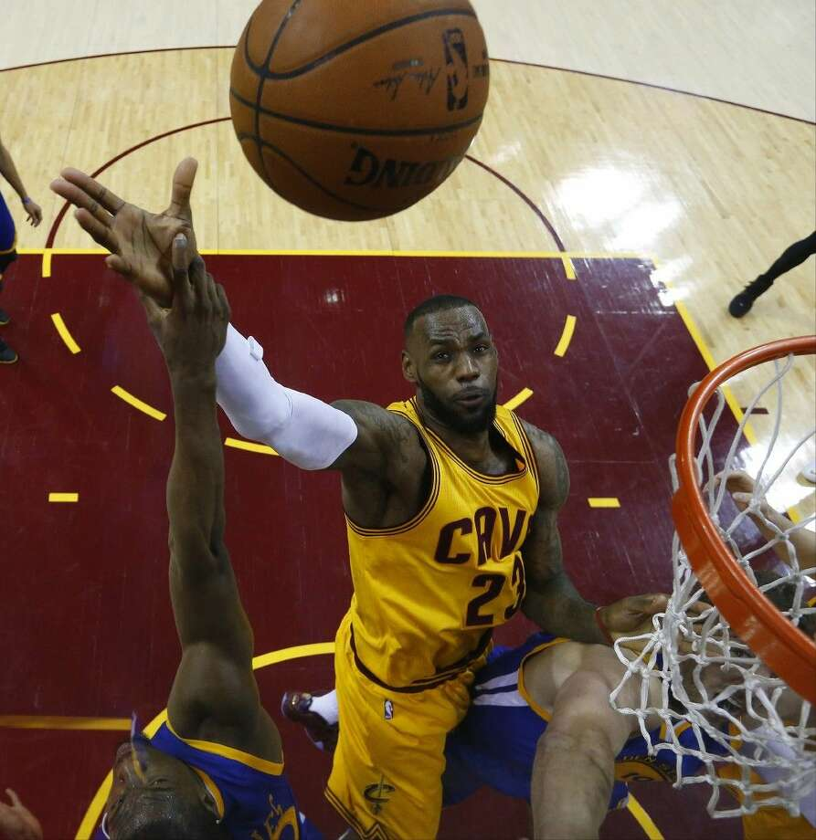 Cavaliers forward LeBron James shoots over Golden State Warriors forward Harrison Barnes, left, during the second half of Game 4. The Warriors won the game 103-82, tying the series at 2-2. Photo: Larry W. Smith