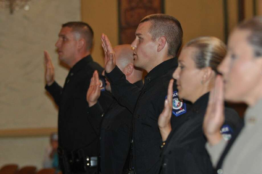 Conroe Police Department recruits are sworn into their positions at the Conroe Police Academy graduation ceremony at the Crighton Theatre on Thursday. Photo: Keith MacPherson