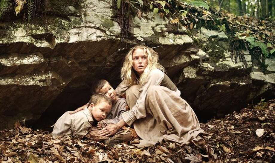 "Lydia (Jenn Gotzon) hides two of the children after their village was attacked by Native Americans in the upcoming movie ""Alone Yet Not Alone."""