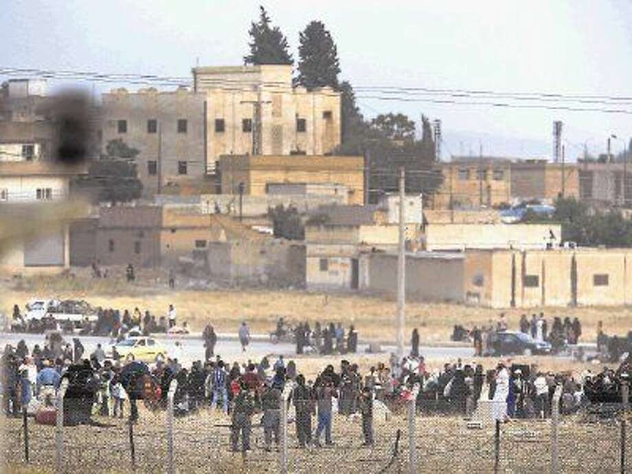 In this photo taken from the Turkish side of the border between Turkey and Syria, in Akcakale, Sanliurfa province, southeastern Turkey, gunmen, bottom, believed to be an Islamic State militants, stand after ordering Syrian refugees waiting on the Syrian side of the border in order to cross, to return back to the city of Tal Abyad, Syria, Saturday. Photo: Lefteris Pitarakis