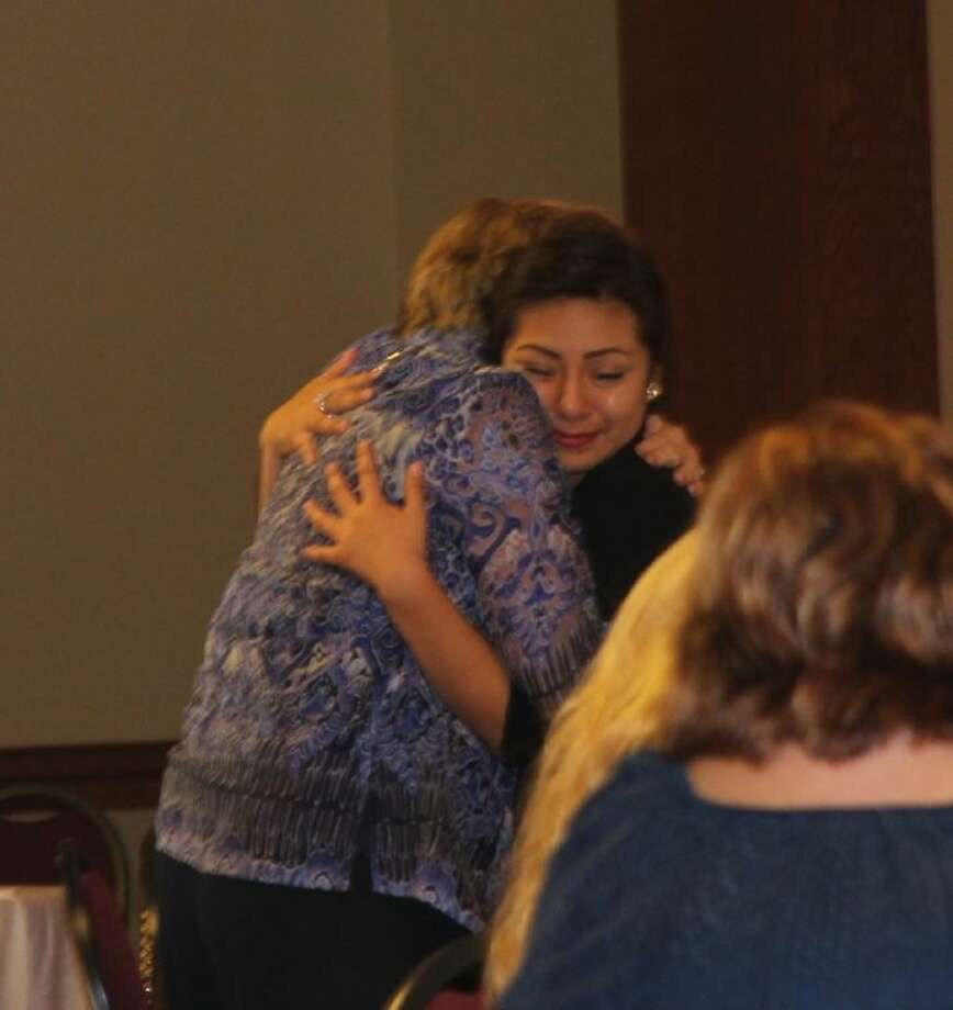 A Conroe ISD high school student embraces her mentor Betty Dozier at the Project Mentor Appreciation Luncheon Thursday at First Baptist Church.