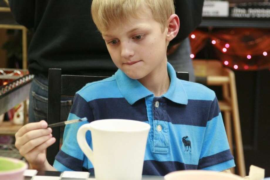 Maplebrook Elementary student Teague Cox paints a mug that will be used in a silent auction for the Texas Business Travel Association golf tournament Oct. 7 which benefits the Addi's Faith Foundation.