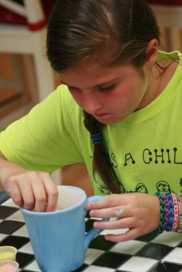 Kingwood resident Laine Raley paints a mug that will be used in a silent auction for the Texas Business Travel Association golf tournament Oct. 7 which benefits the Addi's Faith Foundation.