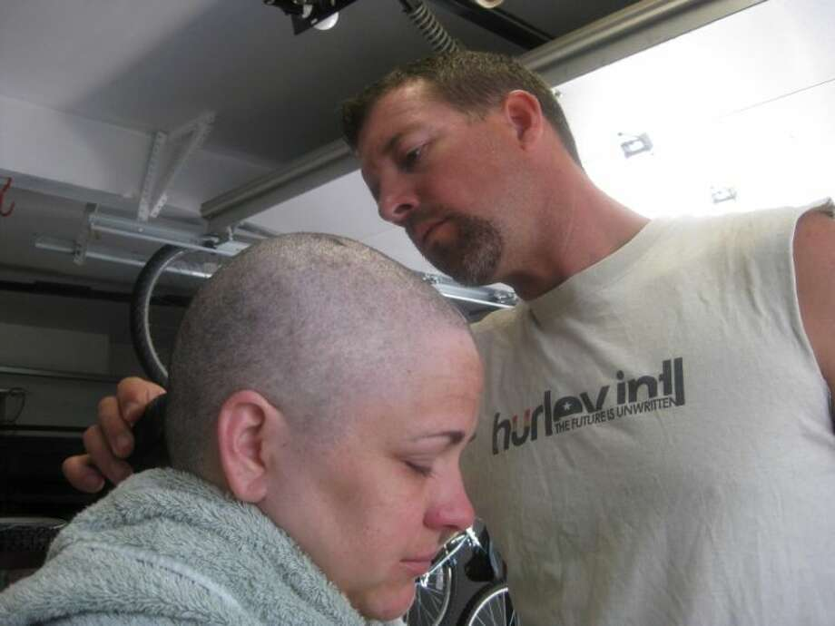 "In this August 2012 photo provided by Arrica Wallace, husband Matthew shaves Arrica's head when her hair was falling out in Manhattan, Kan. Arrica Wallace was 35 when her cervical cancer was discovered in 2011. It spread widely, with one tumor so large that it blocked half of her windpipe. The strongest chemotherapy and radiation failed to help, and doctors gave her less than a year to live. But her doctor heard about an immune therapy trial at the Cancer Institute and got her enrolled. ""It's been 22 months since treatment and 17 months of completely clean scans"" that show no sign of cancer, Arrica Wallace said. Photo: Uncredited"