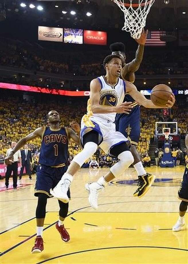 Golden State Warriors guard Stephen Curry (30) shoots against Cleveland Cavaliers guard Iman Shumpert during the first half of Game 5 of basketball's NBA Finals in Oakland, Calif., Sunday. Photo: Bob Donnan
