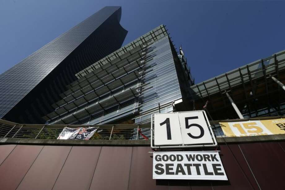 "A sign that reads ""15 Good Work Seattle"" is displayed below Seattle City Hall, right, and the Columbia Center building, left, Monday, after the Seattle City Council passed a $15 minimum wage measure."