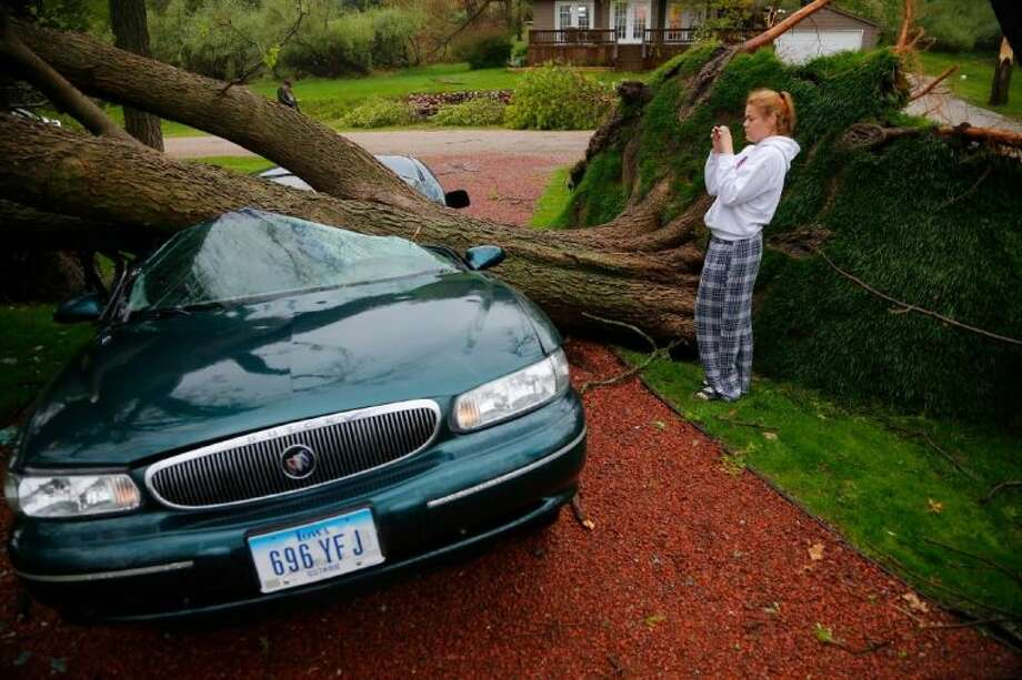 Emilia Merritt, 18, looks at the damage to her car after a tree fell during a storm at her home on Panorama Dr. in Lake Panorama, Iowa, Monday.
