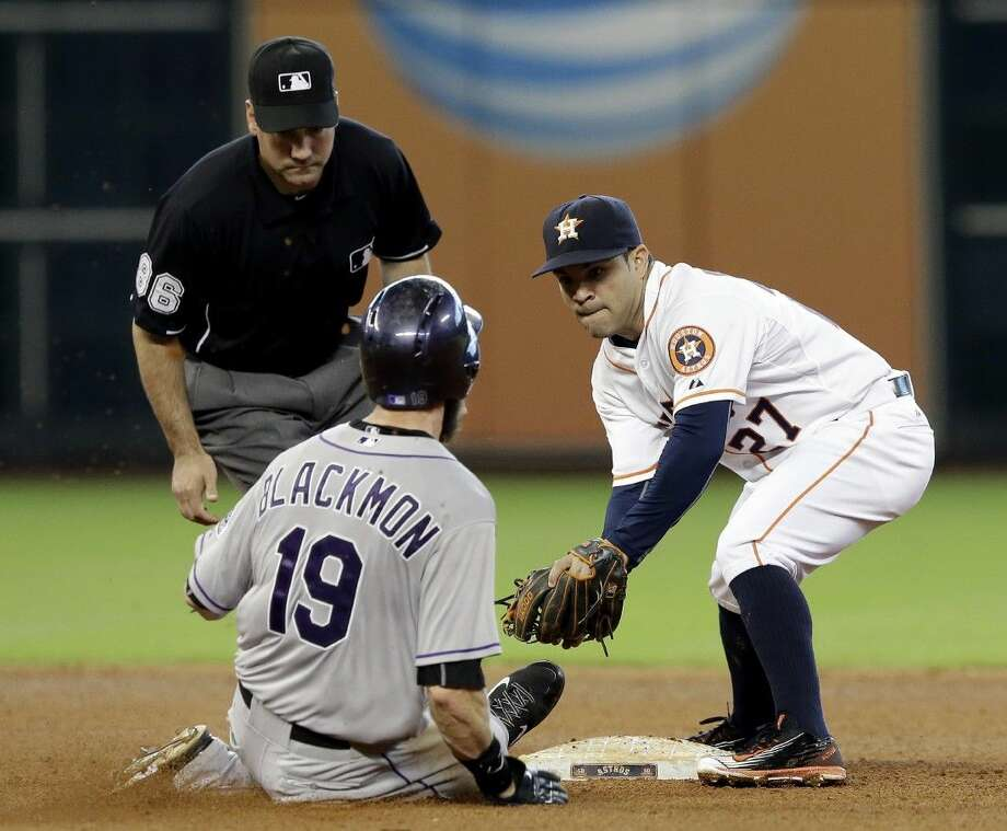 Houston Astros second baseman Jose Altuve (27) tags out Colorado Rockies' Charlie Blackmon (19) as umpire David Rackley watches in the fifth inning Tuesday in Houston. Blackmon was out trying to make it to second on a Corey Dickerson fly out to center field. Photo: Pat Sullivan