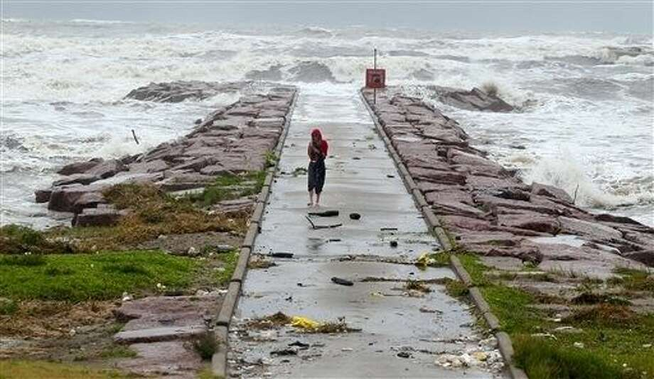 A woman walks back from watching the waves roll over the end of the 29th Street Galveston rock groin Tuesday as Tropical Storm Bill makes landfall. Photo: Rachel Denny Clow